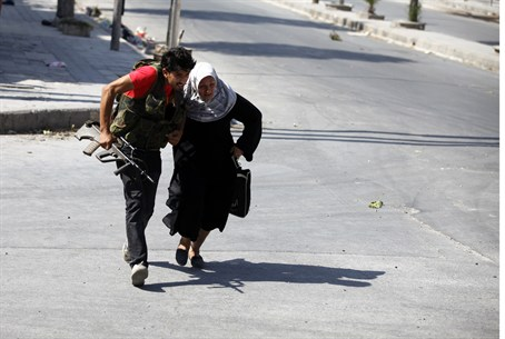 Free Syrian Army fighter helps old woman cros