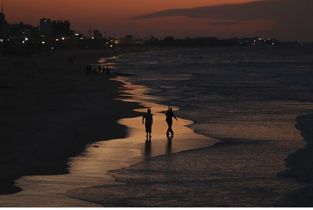Palestinian Arab fishermen walk along the beach of Gaza City