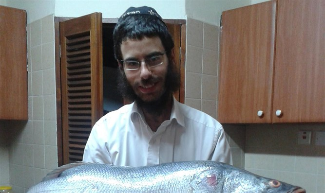 Rabbi Shmuel Notik holding a Nile perch at his home in Nairobi